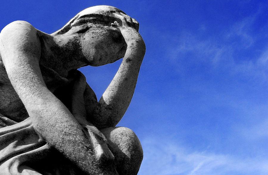 """""""Eu sou os seus sintomas"""" - Fotografia de uma estátua representando uma pessoa sentada, com o cotovelo apoiado sobre o joelho, e a mão sobre a testa."""